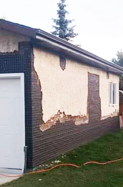 Garage with broken stucco in Edmonton